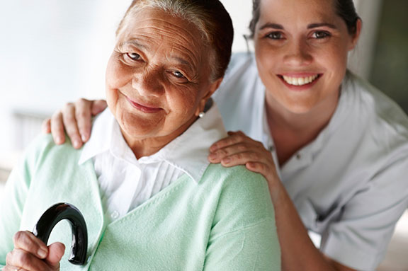 Senior woman with cane and caregiver